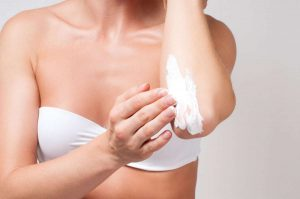 women using cream on her skin